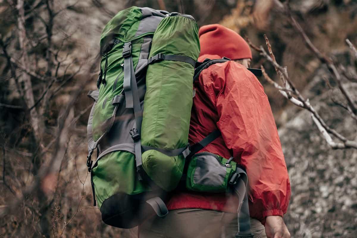 Man wearing EDC backpack hiking in the wood