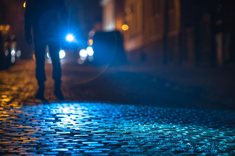 Officer with a flashlight inspecting the road at night