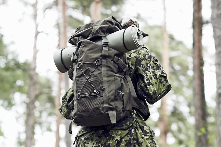 Man wearing tactical backpack hiking in the woods