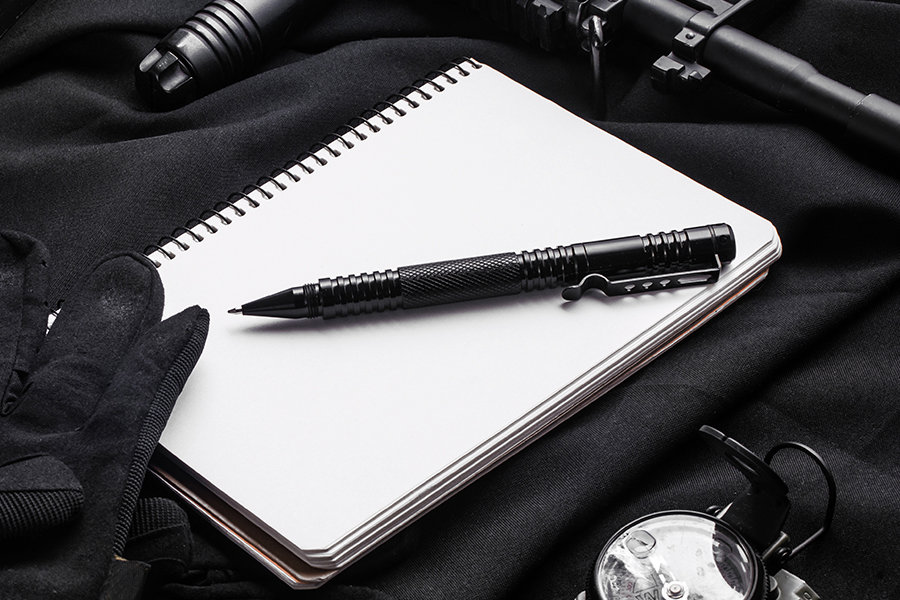 Tactical pen with gloves, rifle and compass on black fabric