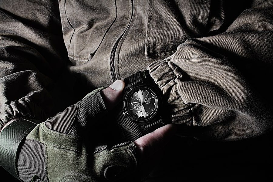 Man holding tactical watch in military clothes
